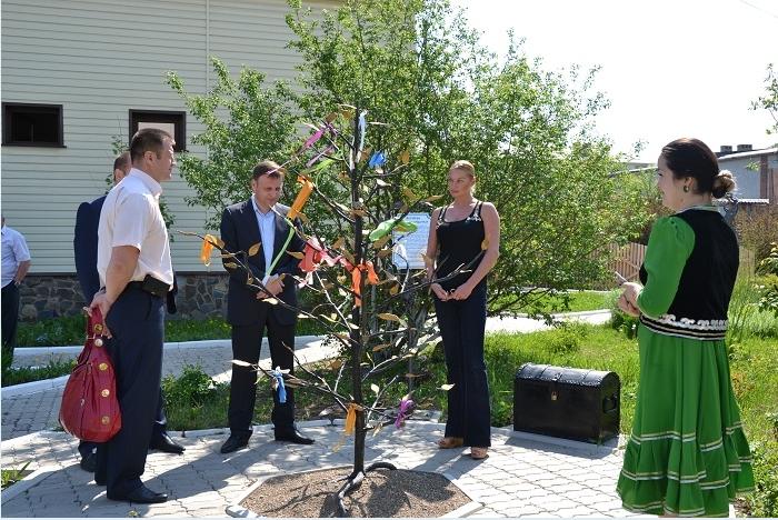 Анастасия Волочкова завязывает ленточки на дереве на счастье, фото август 2015 гастроли в Белорецке и Сибае