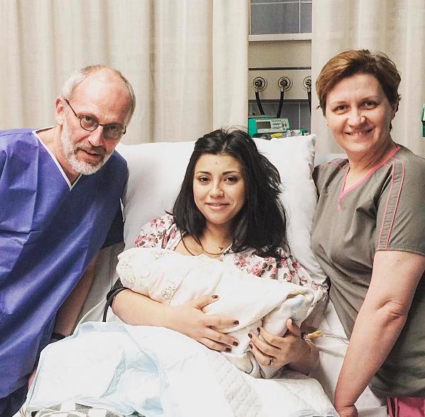 На фото Александр Гордон с женой, новорожденным ребенком и акушером в роддоме